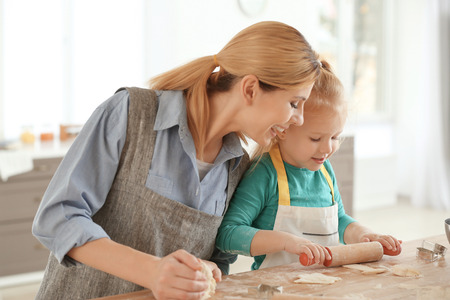Mother and daughter with dough at table indoors Foto de archivo