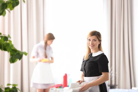 Joven camarera en uniforme trabajando en interiores