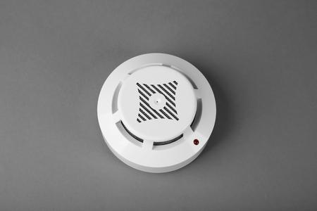 Smoke detector on grey background Stock Photo