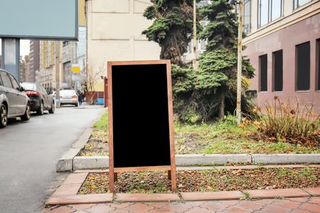 Empty advertising blackboard on city street