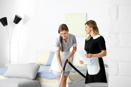 Chambermaid in uniform teaching trainee indoors Stockfoto