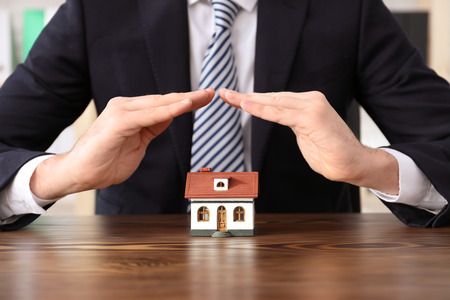Man in office wear protecting house model. Home insurance