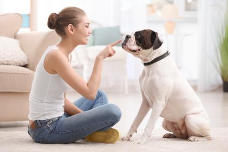 Woman with cute white Boxer dog indoors. Pet adoption Standard-Bild - 112615393