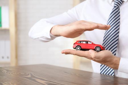 Mann im Büro tragen schützendes Automodell. Fahrzeugversicherung