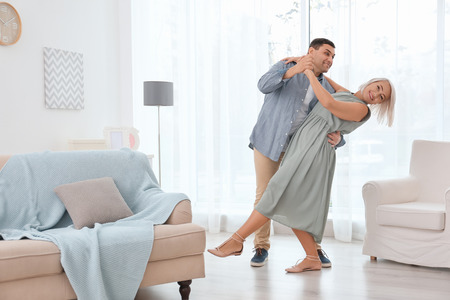 Adorable mature couple dancing together in living room