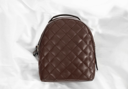 Top view of stylish backpack on fabric background