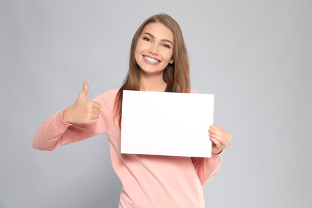 Young woman with blank sheet of paper on grey background Stock Photo