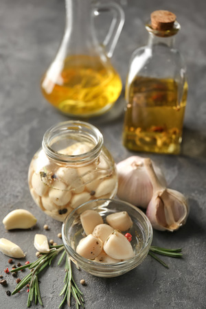 Preserved garlic in glassware on table Banco de Imagens