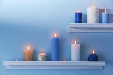 Beautiful burning candles on wall shelves Stock Photo