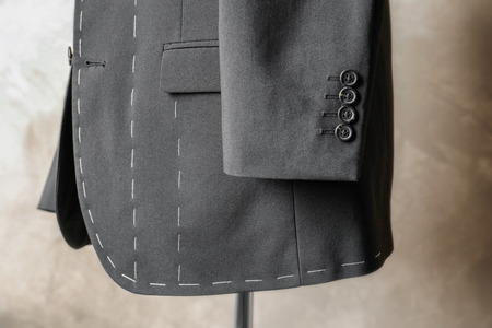 Semi-ready suit on tailor mannequin against light background