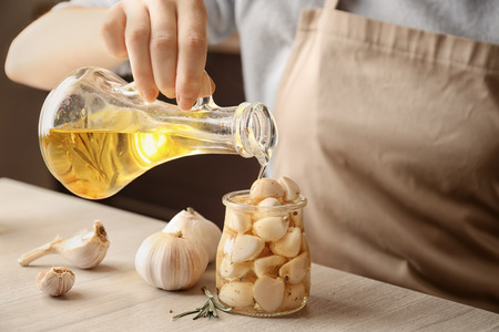 Woman pouring oil into jar with garlic on table, closeup