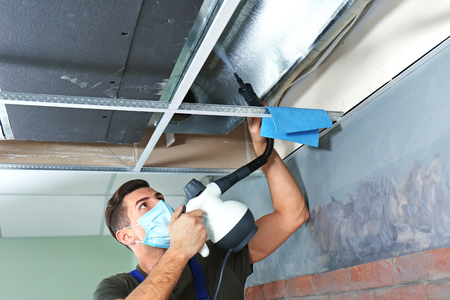 Male technician cleaning industrial air conditioner indoors Foto de archivo