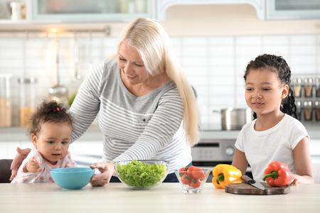 Niñera madura hembra alimentando pequeña niña afroamericana en la cocina Foto de archivo
