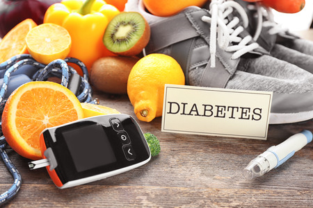 Digital glucometer, lancet pen and fruits on wooden background. Diabetes diet