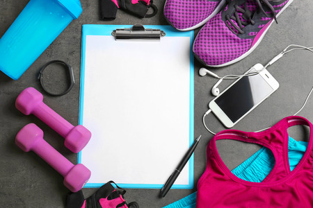 Clipboard with blank paper for exercise plan and gym stuff on grey background. Flat lay composition