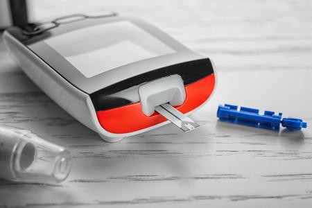 Digital glucometer on light background, closeup. Diabetes management