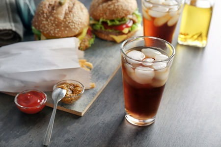 Glass of cold cola with tasty burgers on table
