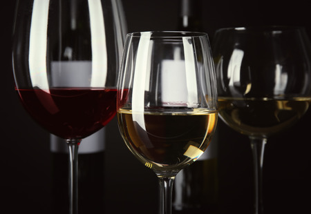 Glasses with different wine on black background
