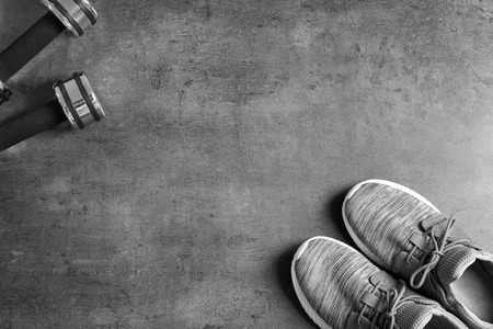 Sneakers and dumbbells with blank space for gym exercise plan on grey background. Flat lay composition