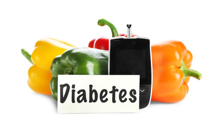 Digital glucometer and vegetables on white background. Diabetes diet