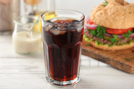 Glass of cold cola with tasty burger on table Фото со стока