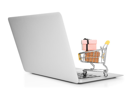 Laptop and small shopping cart with gift boxes on white background. Internet shopping concept
