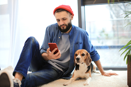 Handsome young hipster with dog at home Фото со стока