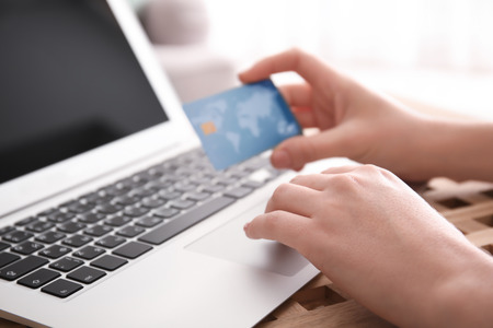 Woman holding credit card while using laptop, closeup. Internet shopping concept 版權商用圖片