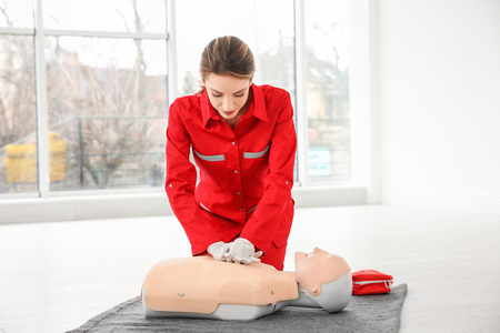 Young woman practicing first aid on mannequin indoors Reklamní fotografie - 112618667