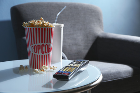 TV remote control and popcorn on table, closeup. Home cinema