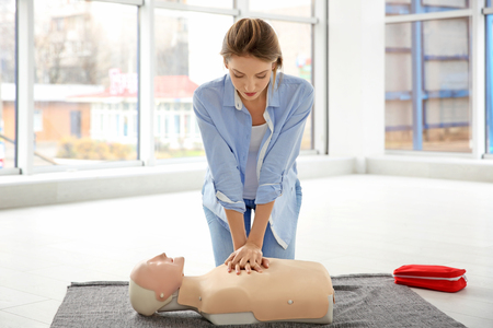 Young woman practicing first aid on mannequin indoors