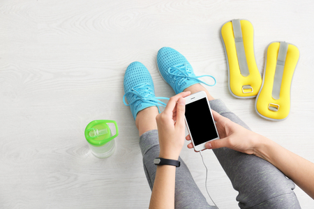 Young woman with mobile phone sitting on floor, flat lay. Ready for gym workout Stockfoto