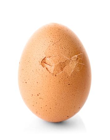 Huevo de gallina agrietado sobre fondo blanco.