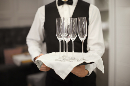 Waiter holding tray with glasses indoors, closeup Reklamní fotografie