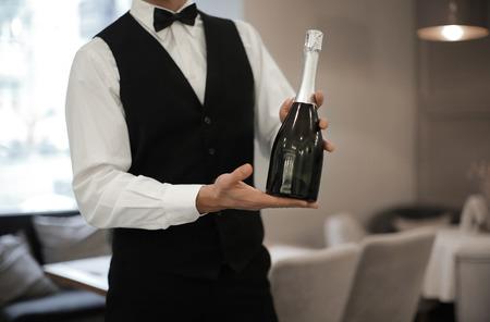Waiter holding bottle of champagne indoors, closeup Stockfoto