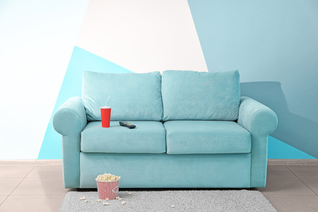 Comfortable couch with popcorn and drink indoors. Home cinema