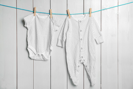 Childrens clothes on laundry line against wooden background Stockfoto