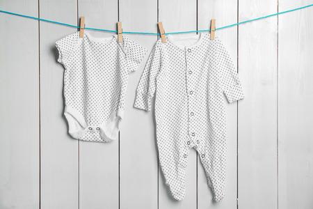 Kinderkleidung auf Wäscheleine gegen hölzernen Hintergrund Standard-Bild