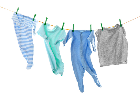 Childrens clothes on laundry line against white background