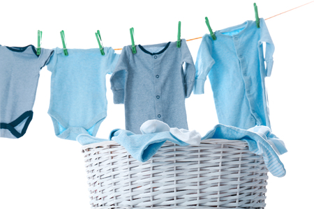 Kinderkleidung auf Wäscheleine und Wäschekorb vor weißem Hintergrund