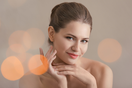 Young woman applying cream onto her skin against blurred background
