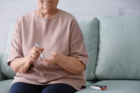 Oudere vrouw met diabetes die de bloedsuikerspiegel thuis meet Stockfoto