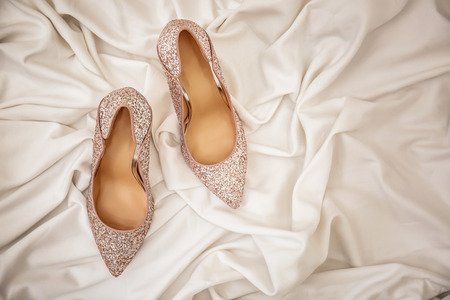 Pair of sparkly female shoes on white fabric, top view