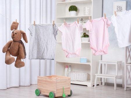Clothes and toy hanging on laundry line indoors