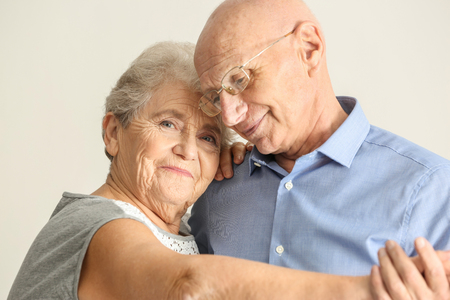 Cute elderly couple dancing against light background Stock Photo