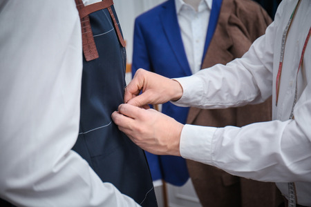 Tailor with client in atelier. Sewing custom made suit