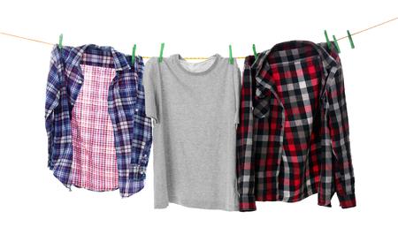 Clothes on laundry line against white background Foto de archivo
