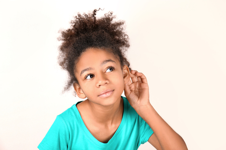 Little African-American girl with hearing problem on light background