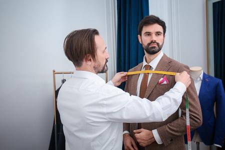 Tailor measuring client for custom made suit in atelier Reklamní fotografie