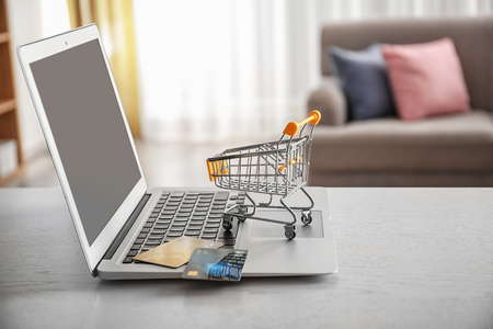 Laptop, small shopping trolley and credit cards on table. Internet shopping concept